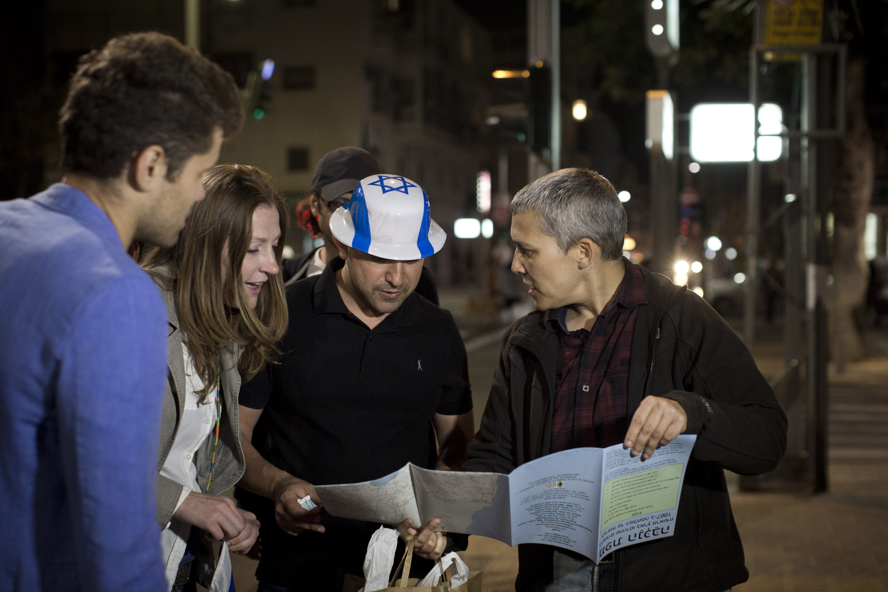 Group including man wearing flag of Israel hat looks at map