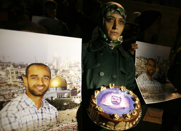 Woman holds a cake, surrounded by posters of prisoner
