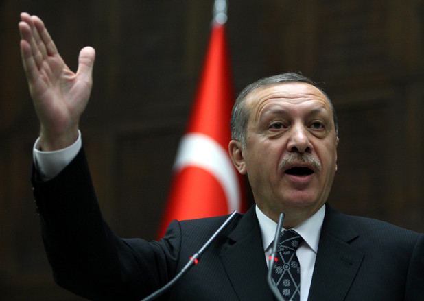 Turkish prime minister seen gesturing with hand in front of flag of Turkey