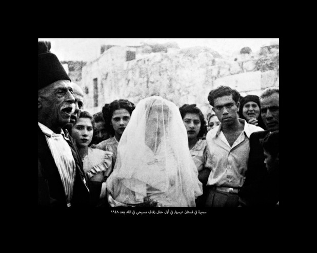 Black and white image of bride in white dress and veil surrounded by people