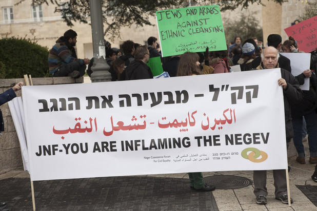 Man holds banner stating in English, Hebrew and Arabic: JNF - you are inflaming the Negev