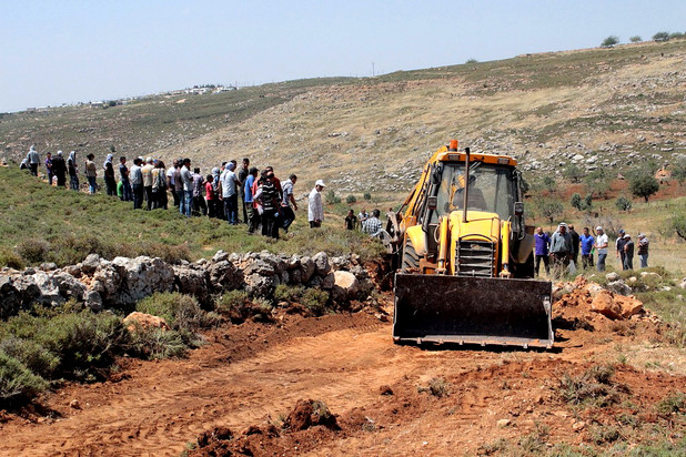 Landscape scene shows crowd of people next to bulldozer