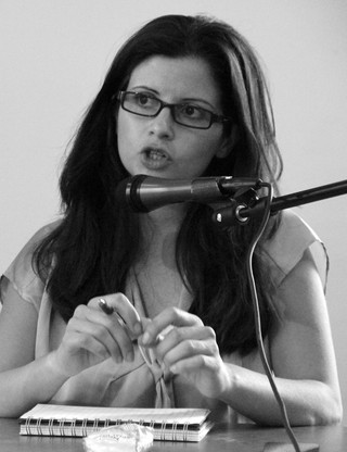 Portrait of seated Abir Kopty speaking into microphone