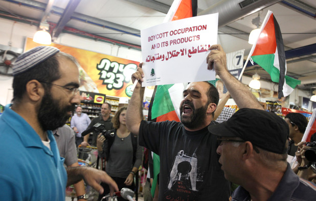 """Man holds up sign reading """"Boycott occupation and its products"""" in Arabic and English"""