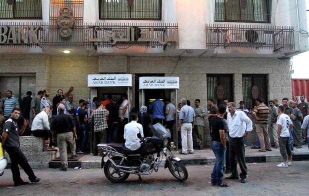 Men queue in front of bank building
