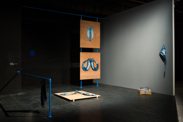 View of dark room with denim configurations displayed on boards