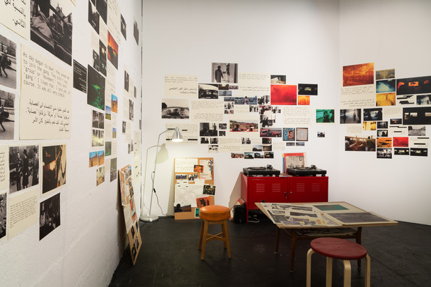 Brightly-lit room with collage of photographs on walls
