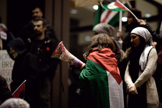 Woman draped in Palestine flag holds a megaphone during nighttime protest