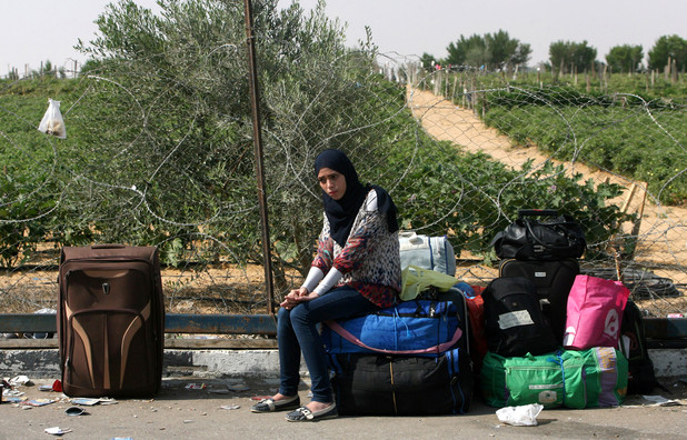 Young woman looks unhappy as she sits outdoors among suitcases