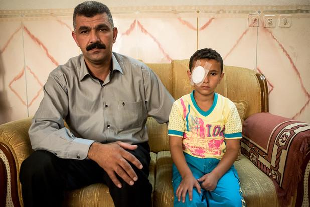 Man sits next to boy wearing cotton bandage eye patch