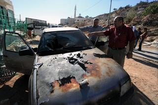 Man gestures towards scorched car