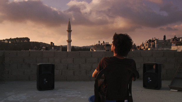 Man on roof sits on chair overlooking city at sunset