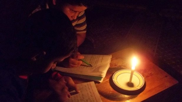 Boys read by candle light