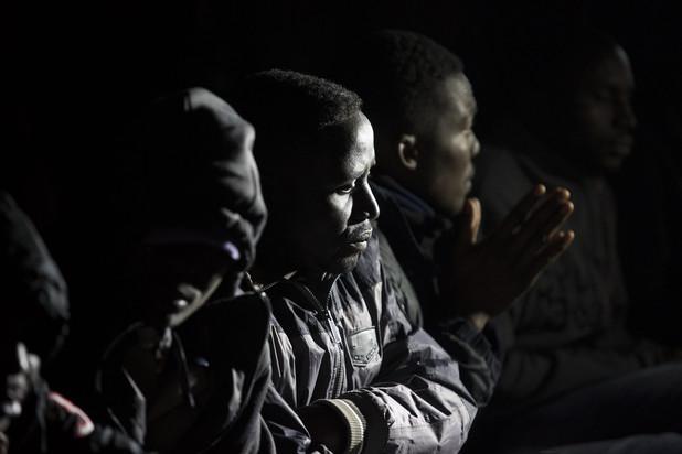Close-up of men wearing winter coats sitting at night
