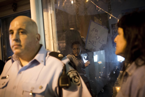 Woman cowers in storefront as Israeli police stand outside