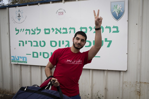 Young man gives carrying duffel bag gives victory gesture with his hand
