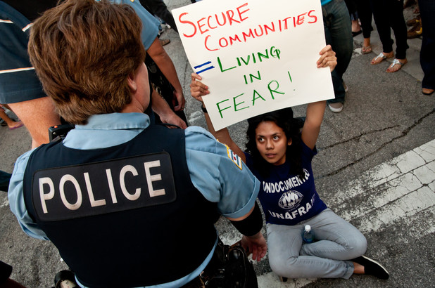 Young woman holding sign sits in street facing police officer