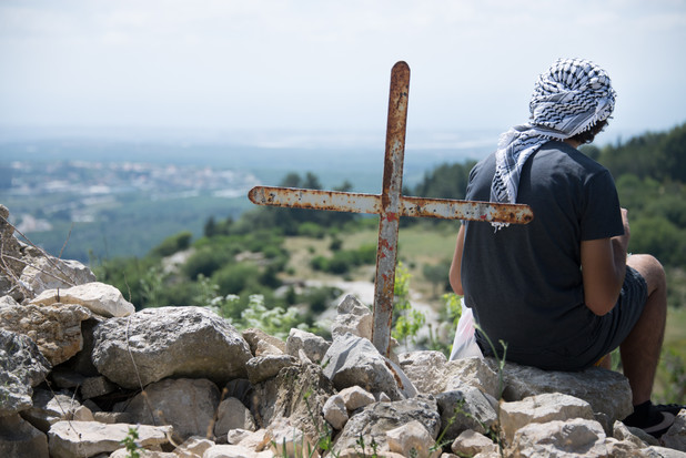 Young man with back to camera sits next to cross on hilltop overlooking valley