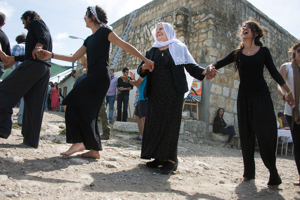 An elderly woman dances with young women in a folk dance line outside old building