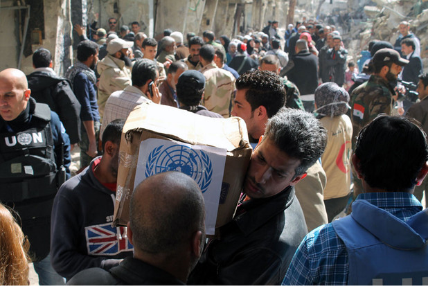 Man carries box of UN provisions amid crowd