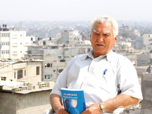 Elderly man sits on rooftop while holding book