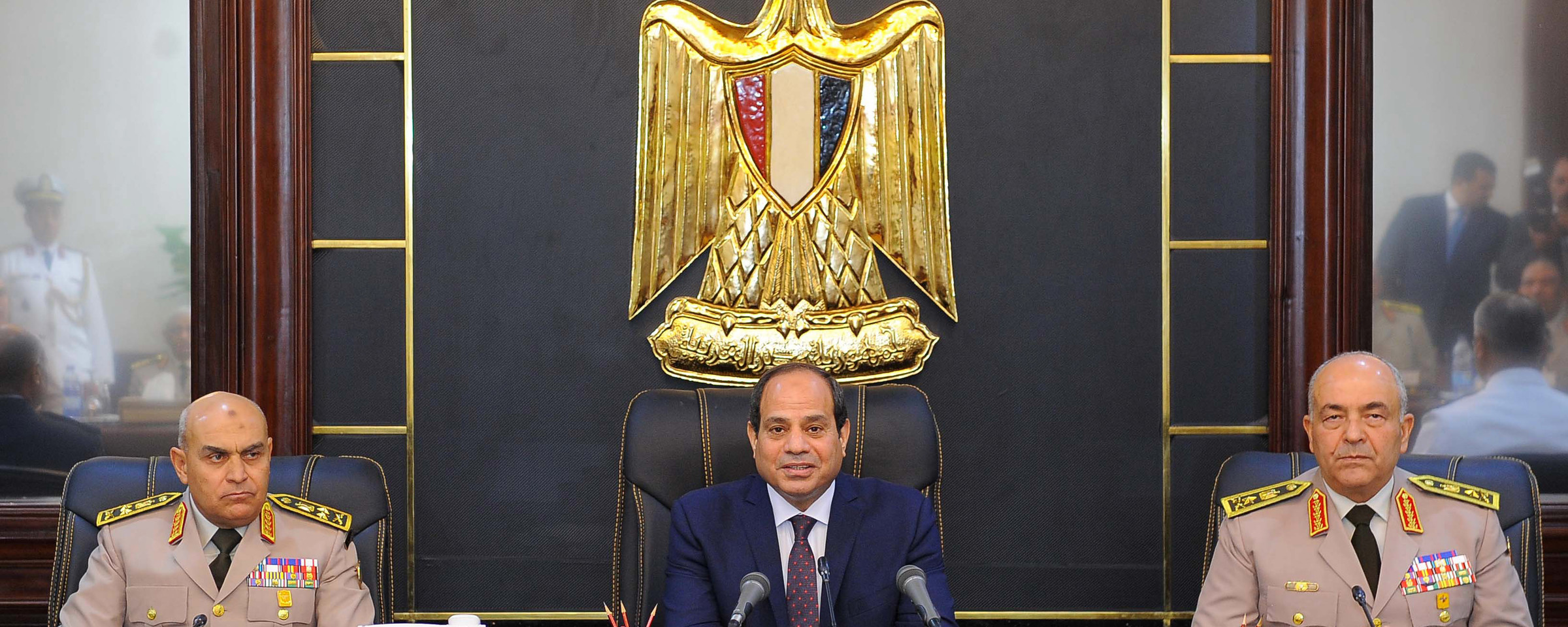 Abdulfattah al-Sisi sits at a desk underneath golden eagle medallion with a military officer on either side of him