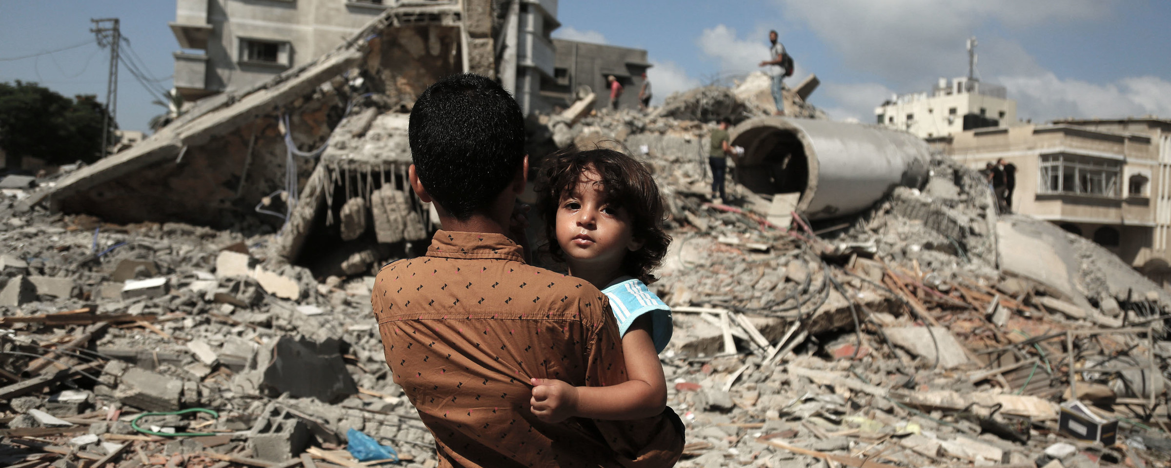 Photo shows back of boy holding small child as the boy stands in front of ruins in urban landscape