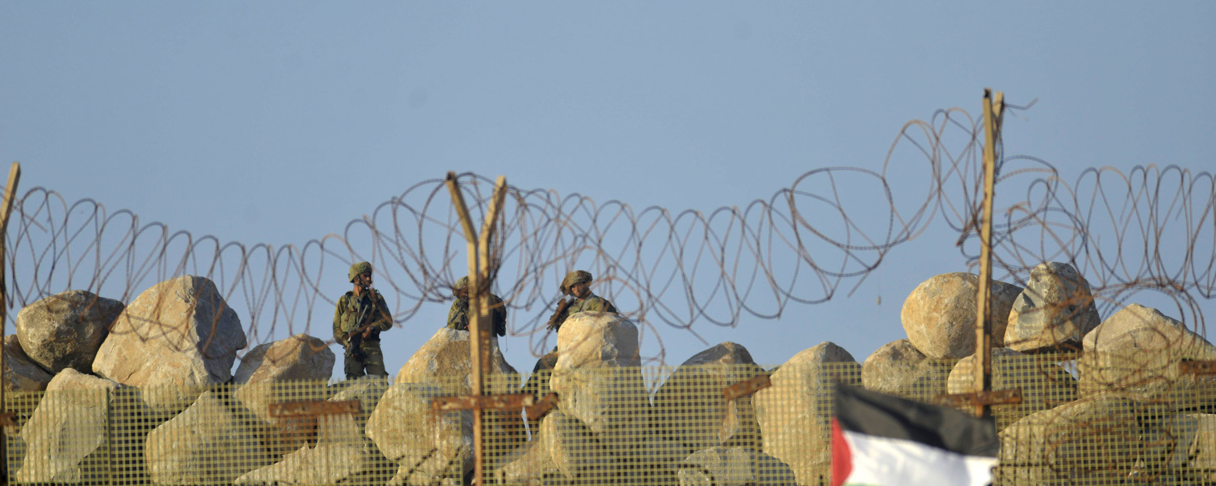 Palestinian protesters stand in front of Israeli soldiers, separated by a barbed wire fence and sandbags