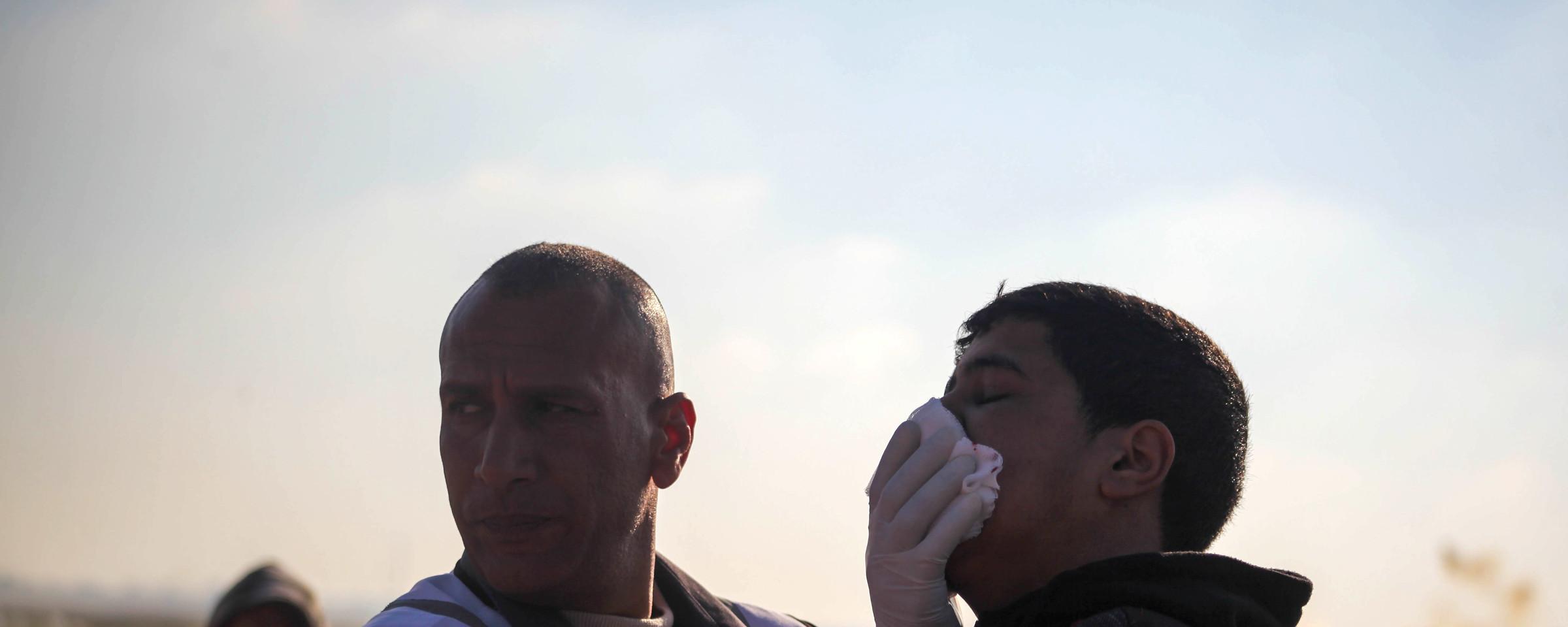 Medic presses gauze against side of man's face