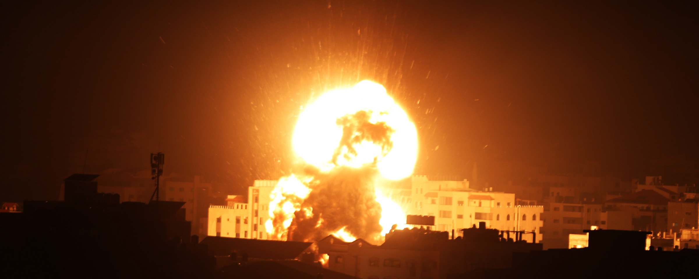 A massive fireball rises over high-rise buildings against a night sky