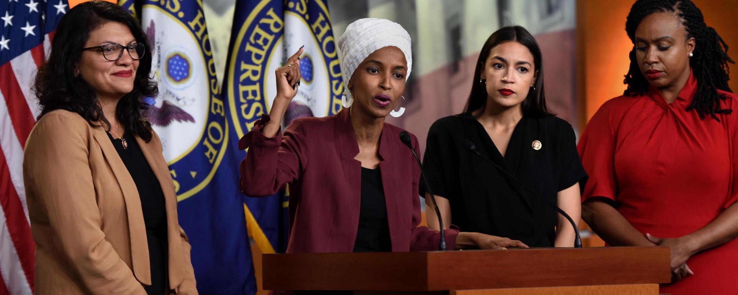 Three women stand around a fourth speaking at podium