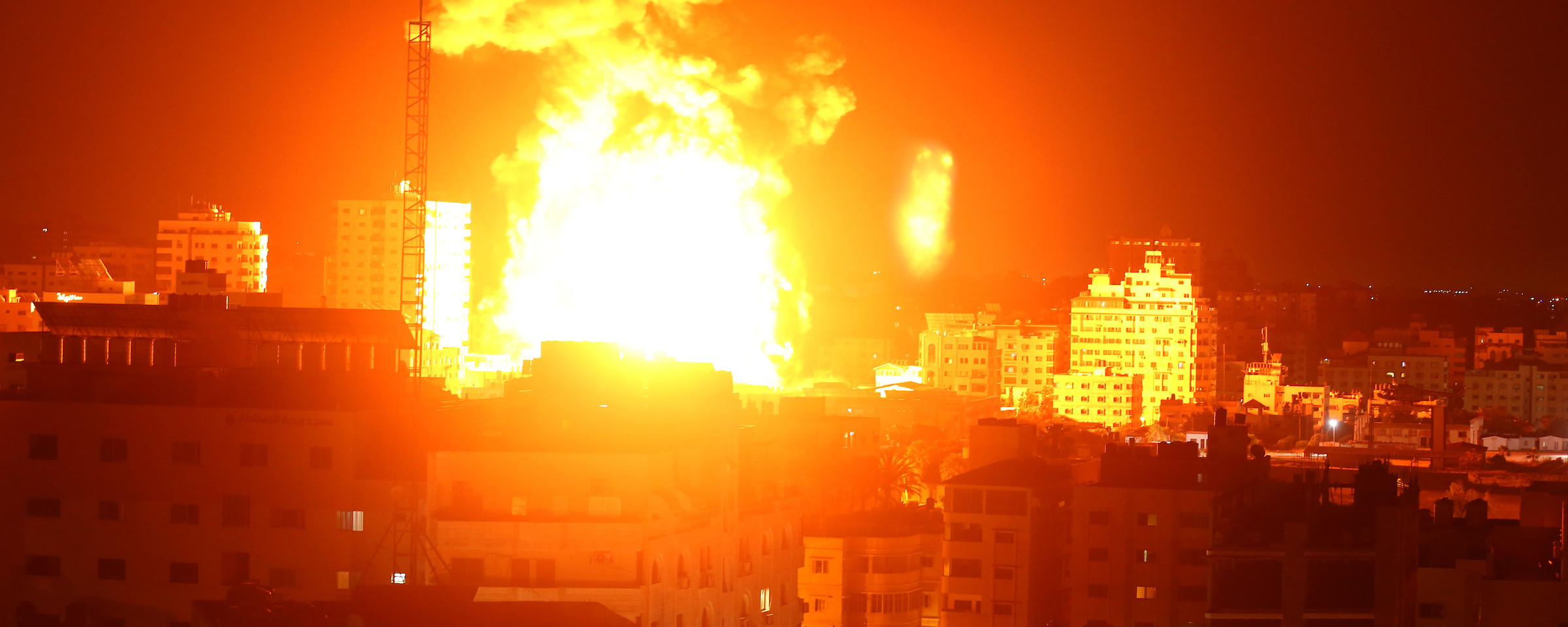 Landscape view of a massive fireball over a city skyline at night