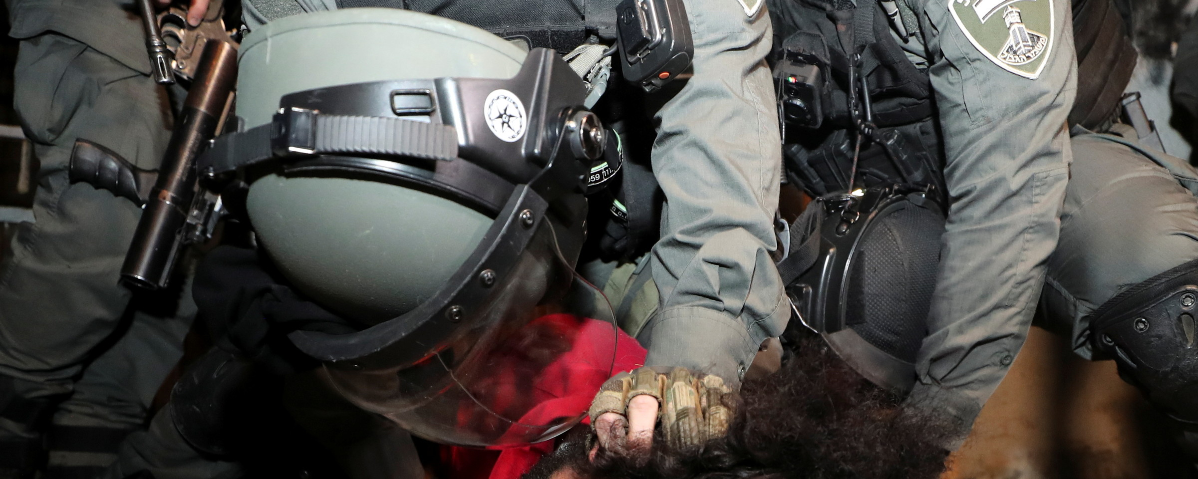 Police in riot gear hold the head of a pinned-down man to the ground