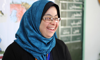 Close-up of smiling woman standing at front of classroom
