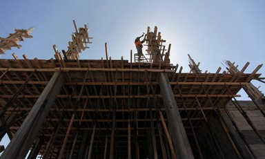 Man hammers on top of partially-constructed building