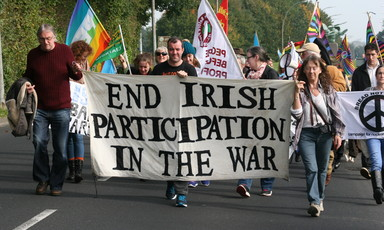 People march while carrying banner reading End Irish Participation In The War