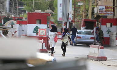A woman and girl walk in front of car at checkpoint painted with colors and emblem of Lebanese flag