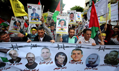 Group of men hold banner showing images of jailed Palestinians in front of crowd of people holding up Palestinian flags and posters of prisoners