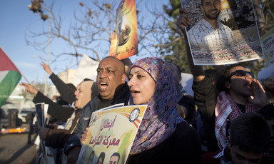 Young woman holds a poster in a crowd of protesters