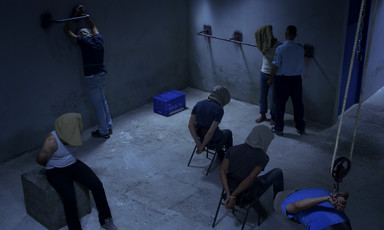 Six men wearing hoods in a dark room are put in various stress positions while a seventh man wearing a guard's uniform stands next to one of them
