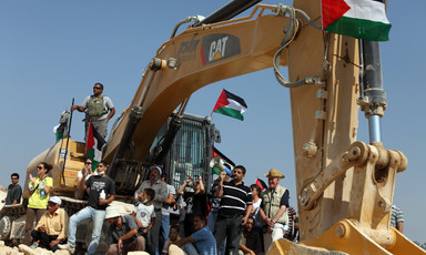 A multigenerational group of people, some carrying Palestine flags, sit around an earth-moving machine with Caterpillar's logo on it and an Israeli soldier standing on top of it