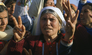 Elderly woman wearing traditional embroidered dress gives victory hand sign among crowd of women