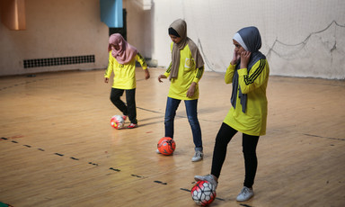 Three girls manipulate footballs with their feet in a gymnasium
