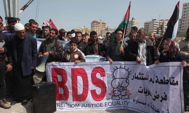 Crowd holds Palestinian flags and large banner reading BDS in English and spelling out boycott, divestment and sanctions in Arabic