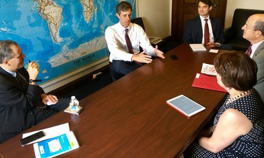 Beto O'Rourke gestures with his hands on a table at which he and four other people are sitting with a map of the world behind him