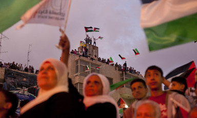Crowd of people wave Palestinian flags, including from rooftop