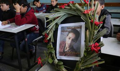 Wreath containing a photo of boy is propped up on chair in schoolroom