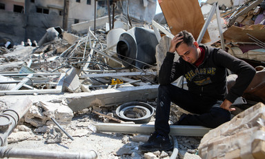 Man holding his head in hand sitting atop rubble