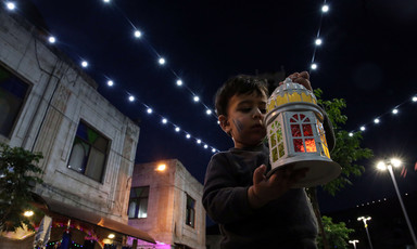 Child holding up a lantern and looking at it.