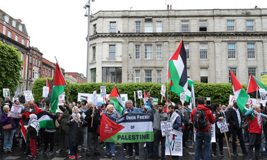 Crowd holding Palestine flags and banners stands outside building